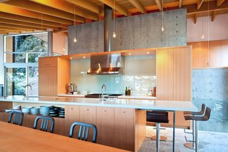 In the dining area, Emeco Navy chairs tuck into a custom fir table with metal legs. Lapalma Thin bar stools offer extra seating around the kitchen counter. Appliances include a Wolf propane range, integrated Subzero fridge, and Miele dishwasher.