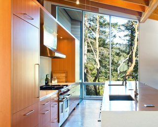 Light streams in through the kitchen from massive, floor-to-ceiling windows that offer peaceful views of the outside foliage.