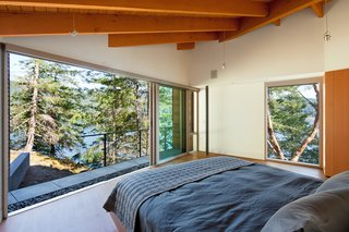 """The path stops at the master bedroom, where a completely glazed end wall frames the wildflower clearing. """"This pathway purposefully links together the architecture of internal rooms and outdoor spaces with discoveries of the site's varied landscape,"""" the architects say."""