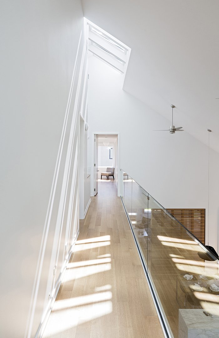 Hallway and Light Hardwood Floor Strategic site planning and smart technology help the 3,200-square-foot Great Gulf Active House achieve hyper-efficiency. The Toronto-based architecture firm, superkül, used triple-glazed windows; a solar hot water system; zoned heating; a fully automated HVAC system, skylights, and roller shades; LED lights; and spray foam insulation, among other green strategies.  Bold Suburban Homes by William Harrison from This Super Smart, Super Green Prefab May Be the Future of Suburban Living