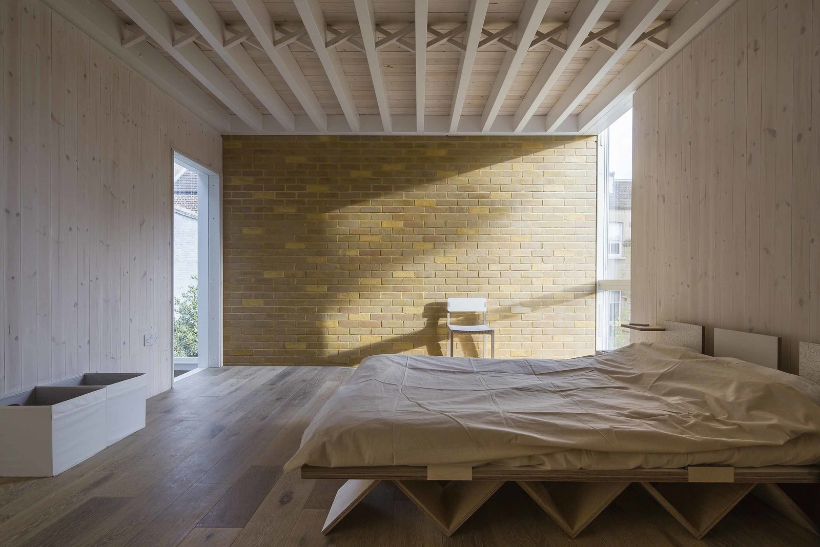 Structural lines are on full display in the bedroom, where ceiling beams and a plywood bed frame catch the eye.  40+ Homes With Exposed Beams: Rustic to Modern by Luke Hopping from An Award-Winning London Addition Balances New and Old
