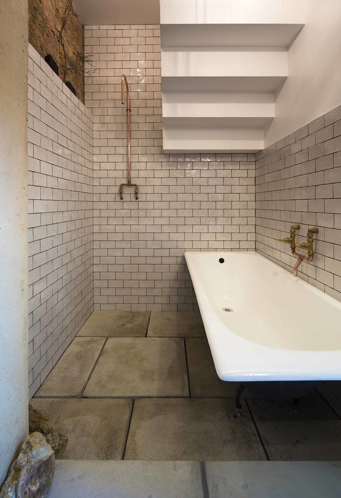 Bath Room and Concrete Floor In the bathroom beneath the stairs, copper fixtures and subway tile feel at once sensitive to the home's roots and very of the moment. It is this attention to cohesiveness that the Don't Move Improve! award seeks to recognize.  Bathroom from An Award-Winning London Addition Balances New and Old