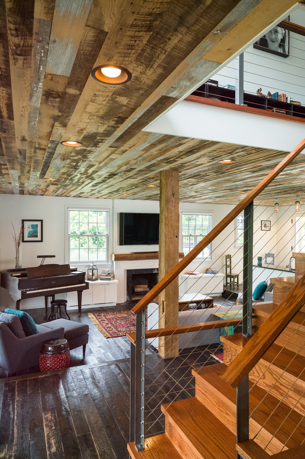 """The staircase works as a visual transition from the cozy first level to the more modern second floor. When standing downstairs, the staircase pulls away from the dark anchoring floorboards with angled steel beams, stainless steel cables, and wood caps. """"It's thin and light so that it wouldn't impede connection to the first floor,"""" says Michael. """"It's meant to be pretty modern, but the wood cap softens the look a little, and makes the experience of touching the railing softer.""""  Photo 4 of 8 in A Loving Renovation Updates a Rustic Family Home with Reclaimed Materials"""