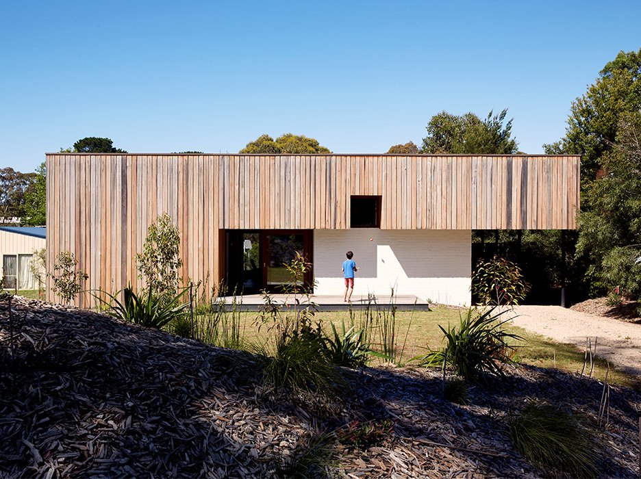 Rachel Nolan and Steven Farrell's weekend house is located a couple of blocks from the beach on Australia's Mornington Peninsula. Built with passive principles in mind, the low-slung structure features double-thick brick walls for thermal massing. The vertical wood cladding is unfinished spotted gum, a local timber. Tagged: Exterior, House, and Wood Siding Material.  Photo 1 of 11 in Simplicity Rules at this Family Beach House Designed to Double as a Rental