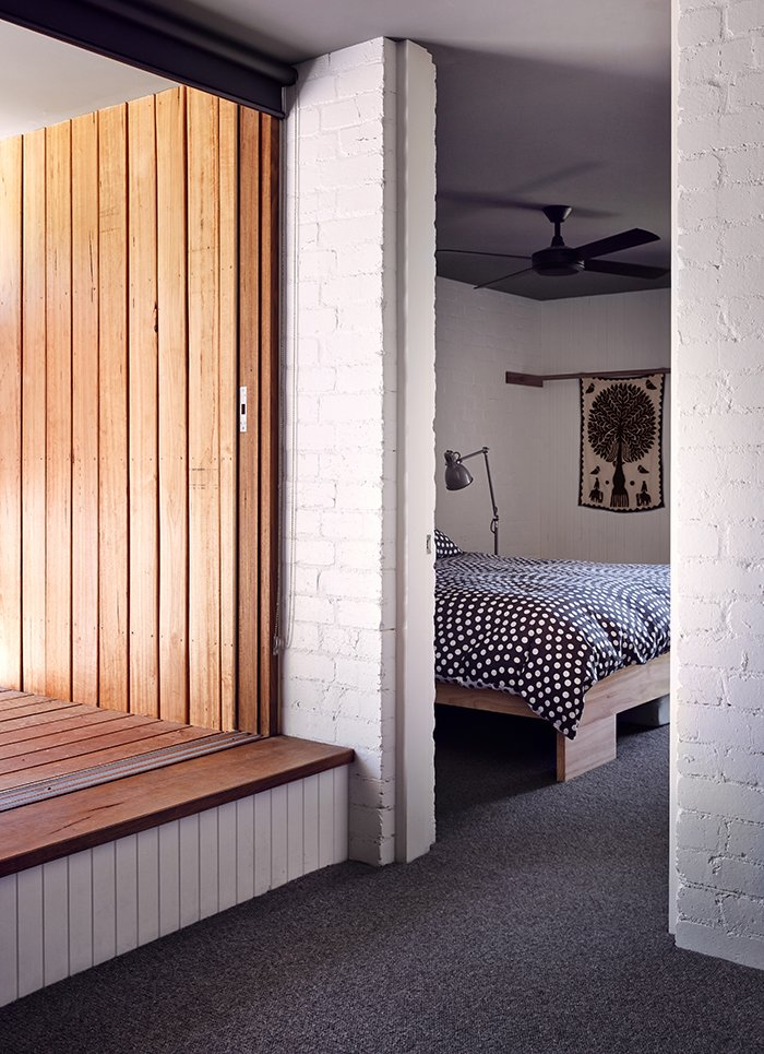 Bedroom, Bed, Floor Lighting, and Carpet Floor A Hunter Pacific fan cools the master bedroom, which has a custom hardwood bed.  Photo 6 of 11 in Simplicity Rules at this Family Beach House Designed to Double as a Rental