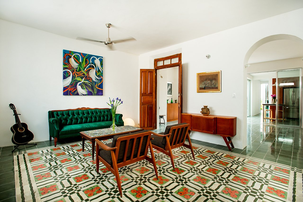 """Eye-catching patterned tile offers a bold focal point in the living room. Antique midcentury chairs and a credenza furnish the space. In the living room and beyond, the architects purposefully avoided an open floor plan in favor of a collection of traditionally defined spaces. """"Every space has its own character and belongs to a whole simultaneously,"""" says project architect Atahualpa Hernandez Salazar.  Casa Mérida by Sarah Akkoush"""