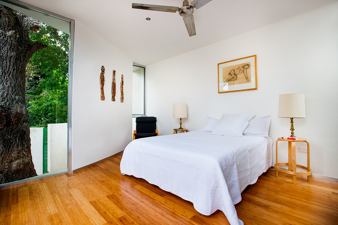 """Although the entire original structure of the house was preserved, an east-side addition adds space and is a distinctly modern counterpoint to the original home. The new construction, including the master bedroom, curves organically around the sapote tree, and the tree, says Salazar, """"becomes the main character.""""  Bedrooms by Dwell"""