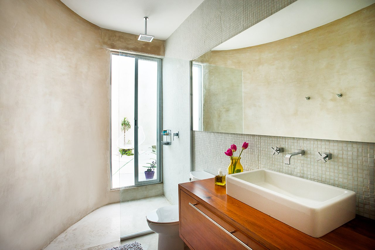 In the upper floor bathroom, streamlined materials highlight the unique and irregular shape of the space. White polished concrete is used for both walls and floors, and frosted Venetian tiles are used in the shower area. Tropical Tzalam wood adds warmth to the space.  Casa Mérida by Sarah Akkoush