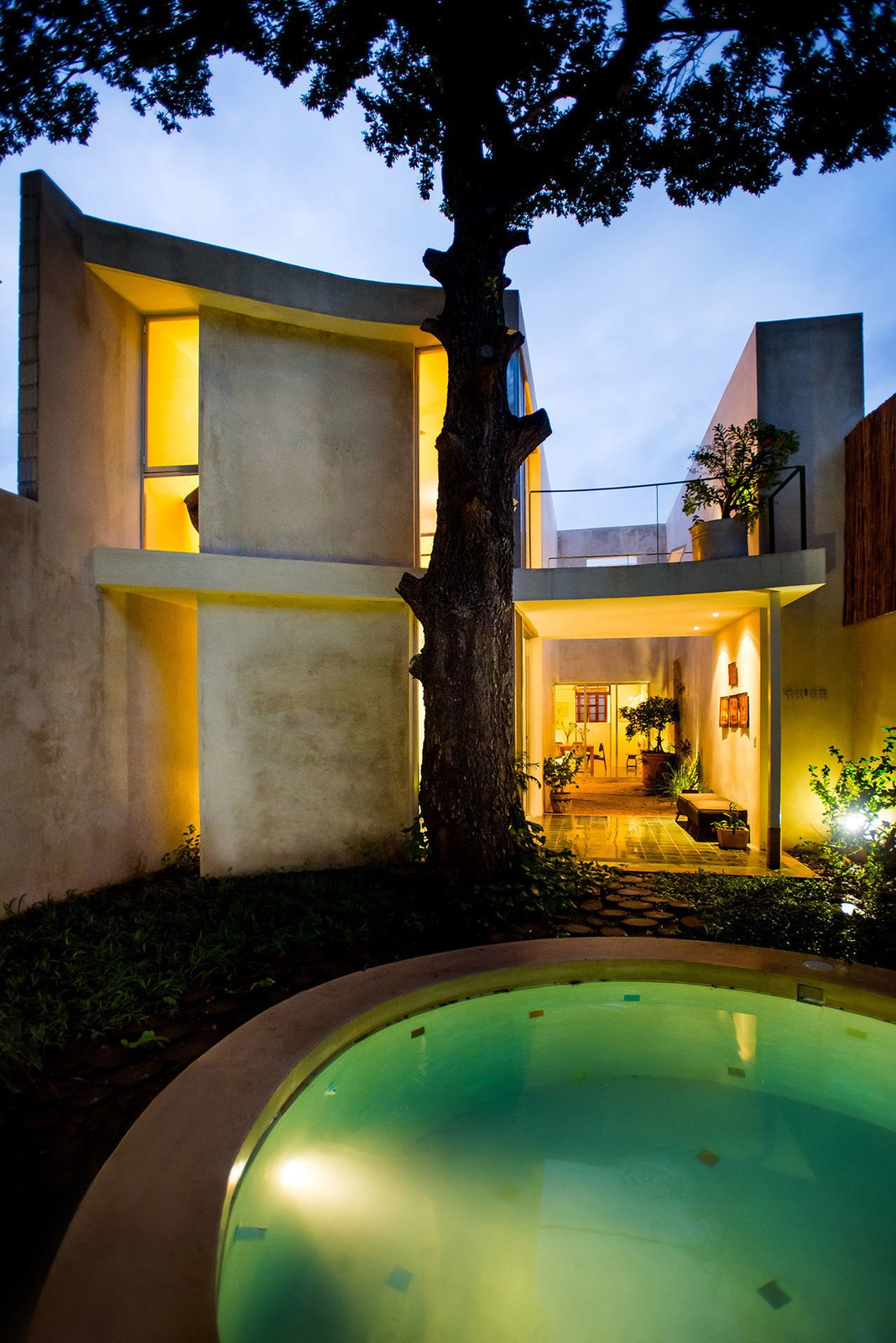 The grand and stately tree is the unchallenged star of the backyard. The round pool, made of made of white polished concrete and handcrafted cement floor tile, smartly pairs with the curved, east-side elevation of the home.  Casa Mérida by Sarah Akkoush
