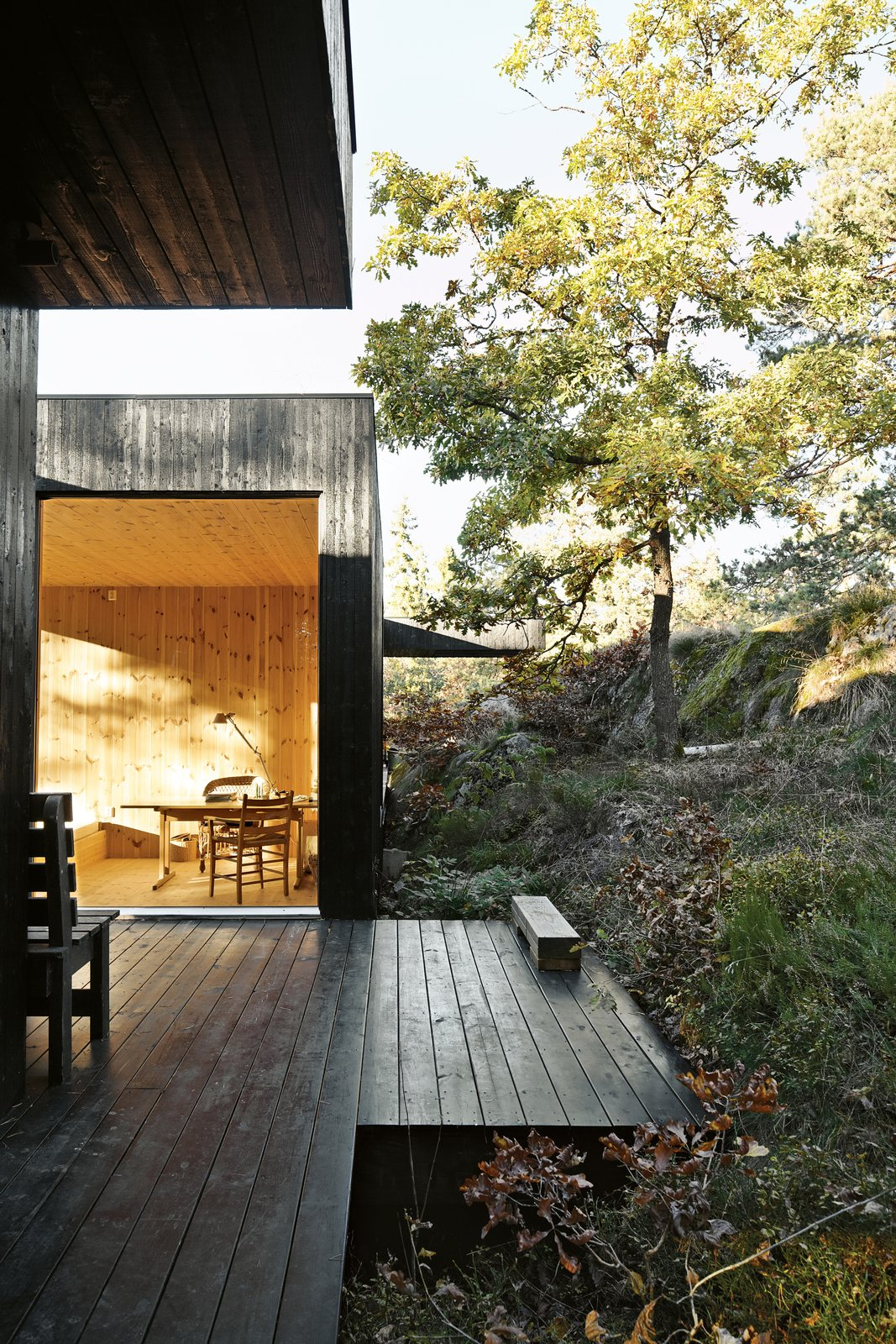 "Outdoor, Side Yard, Wood Patio, Porch, Deck, Boulders, Trees, Hardscapes, and Shrubs The house is divided into three sections connected by a series of outdoor galleries. ""When I walk from one room to another, I have to go outdoors and feel the weather and nature—rain, cold, and sun,"" says Sævik.   Instead of emphasizing the expansive panorama of oak, pine, and aspen trees, the house frames select views—a move inspired by Japanese design.  Cabins from Japanese-Style Homes with Engawas"