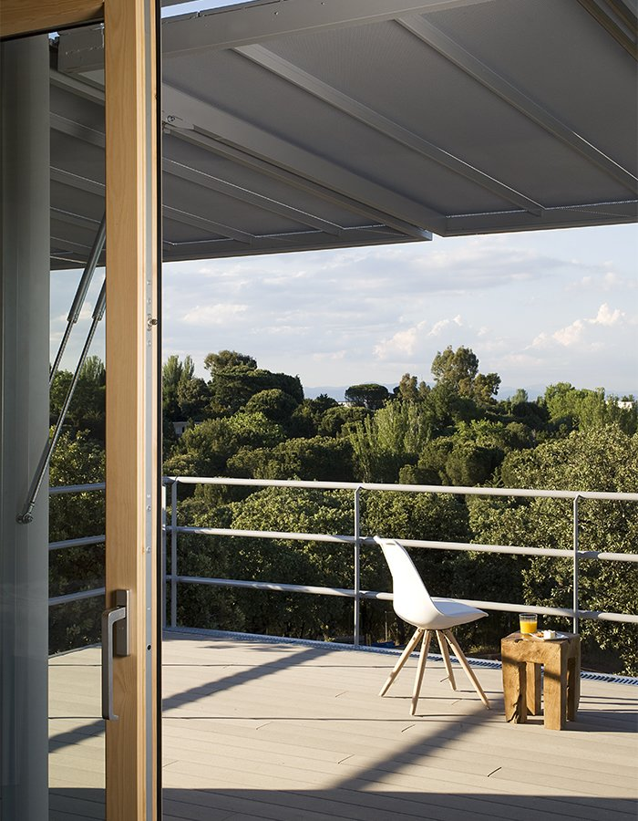 Outdoor, Wood Patio, Porch, Deck, Trees, Rooftop, Metal Fences, Wall, and Side Yard Automated shutters overhead provide privacy when closed and shade the deck when open.  Photo 2 of 9 in This Futuristic Prefab in Spain Has All the High-Tech Gizmos of a Spaceship