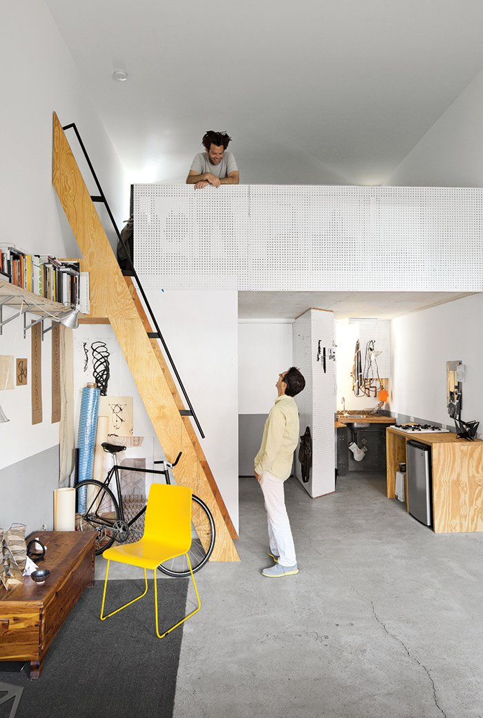 Living Room, Chair, Shelves, and Wall Lighting From the mezzanine of his 450-square-foot apartment at La Esquina, an eight-unit live/work building in San Diego's Barrio Logan neighborhood, designer, artist, and Woodbury University professor Patrick Shields chats with fellow professor Hector Perez, who spearheaded the project.  Photo 1 of 14 in San Diego Teaches Us How Micro-Living Can Thrive