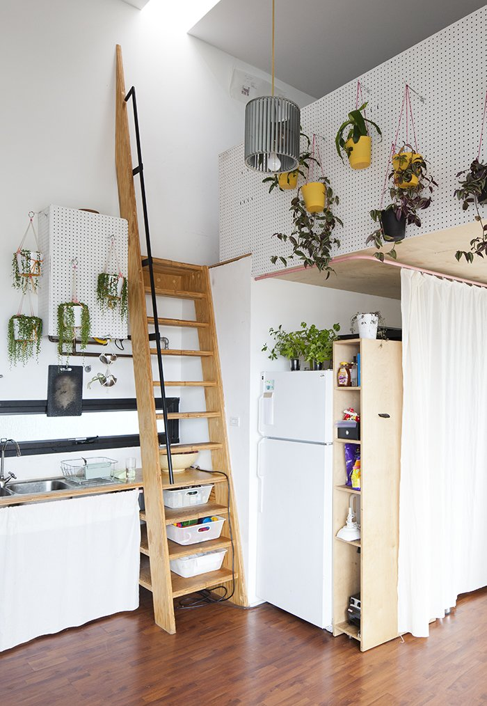 """Kitchen, Medium Hardwood Floor, and Refrigerator """"Food generally plays a part in the exchanges,"""" explains Benson, """"so the adjacent kitchen plays its part in lending to that [collaborative] atmosphere.""""  Clever Loft Spaces for Small Places by Diana Budds from San Diego Teaches Us How Micro-Living Can Thrive"""