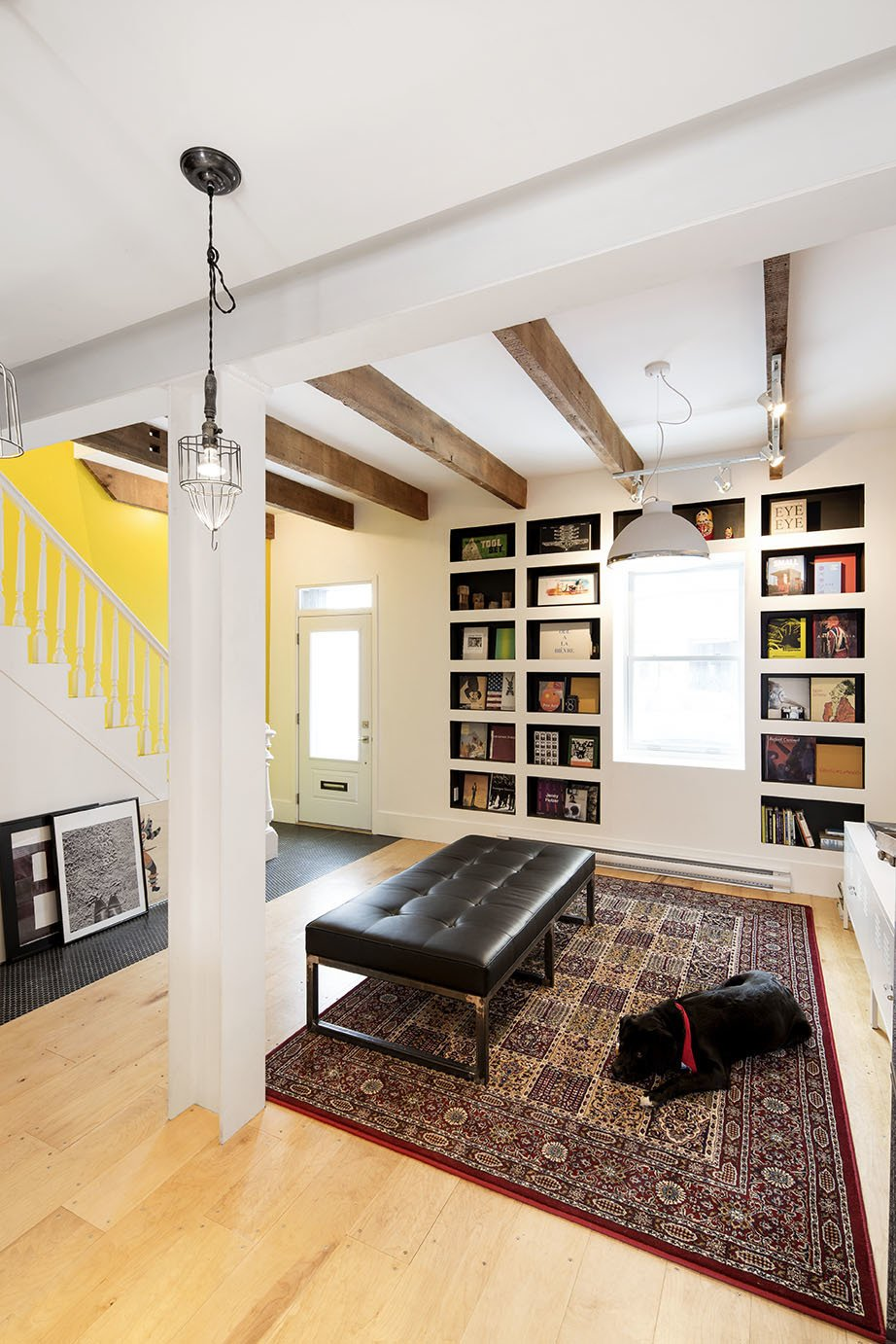 Living Room, Plywood Floor, Bench, and Bookcase Locally sourced Canadian plywood was used for the flooring throughout the home, and all doors and windows were replaced with low-energy upgrades. The couple shares their space with guide dogs they foster through a local organization.  An Old Row House in Montreal Gets a Colorful Modern Upgrade by Sarah Akkoush