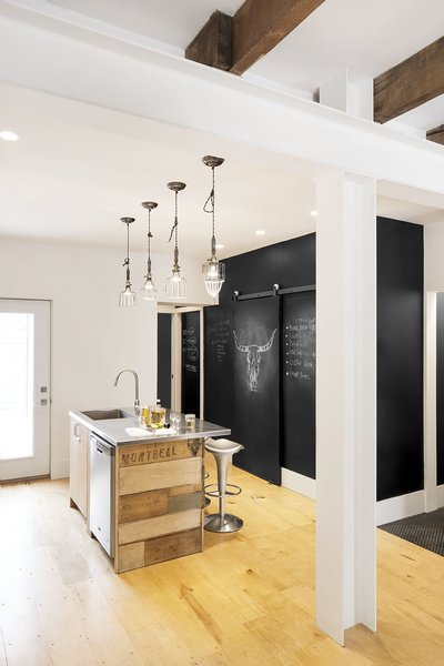 The couple's kitchen is an exercise in both sustainability and creativity. The island is wrapped with reclaimed scrap wood uncovered from the house during demolition. Chalkboard walls provide a whimsical canvas for graphic images and notes.