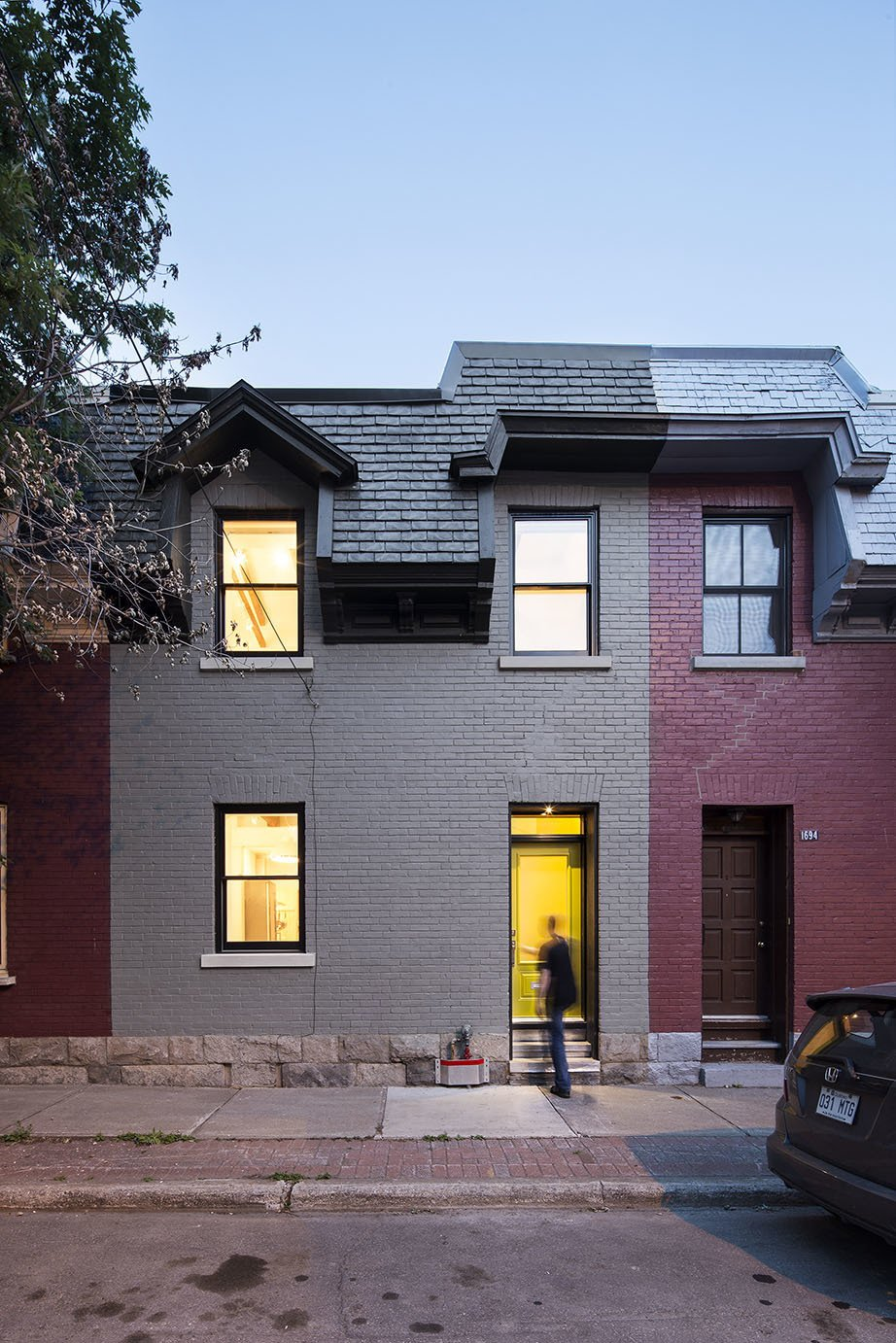 "The outside of the home is illuminated at night. The crumbling slate roof was replaced with new composite tiles made from recycled rubber. The couple says their goal is to ""help revitalize transitioning neighborhoods, one building at a time.""  Row, Row, Row Your House: 5 Urban Row House Renovations We Love by Heather Corcoran from An Old Row House in Montreal Gets a Colorful Modern Upgrade"
