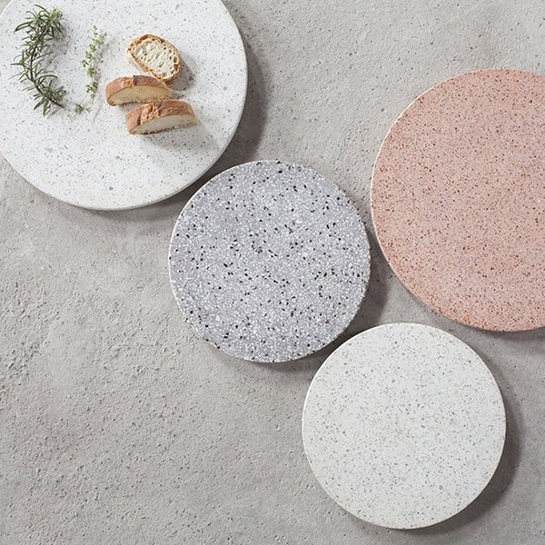 The Terrazzo Platter from Serax is a sophisticated kitchenware accent, and can be used as a serving tray, board for cheese and charcuterie, or even as a centerpiece on a dining room table—it can present tea lights, a vase of flowers, or center another accent. Terrazzo is a composite material that is available in a range of colors and tones and features a distinctive speckling. The material is both striking and simple, making it an excellent choice for different decors. On a wood table, the platter will provide material interest, while on a stone counter, the platter creates a subtle contrast. Available in two sizes and tones, the Terrazzo Platter is a simple and refined serveware piece.
