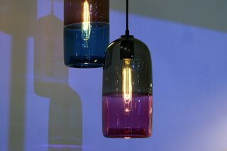 Over on the Australian Pavilion at 100% Design, Melbourne-based designer Mark Douglas exhibited a line of two-toned blown glass pendant lamps fitted with incandescent bulbs.