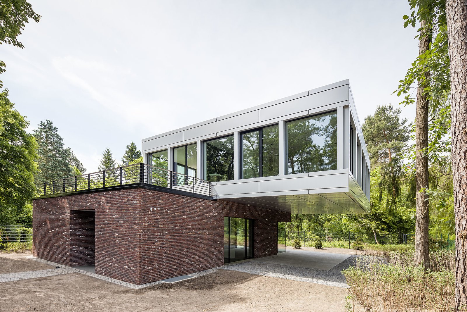 "Outdoor The lower level is covered in traditional red brick, while the upper level consists of coil-coated aluminium sheet with large glass panes.  Search ""5 gravity defying cantilevers"" from Striking Cantilevered Home Pairs Brick and Aluminum"