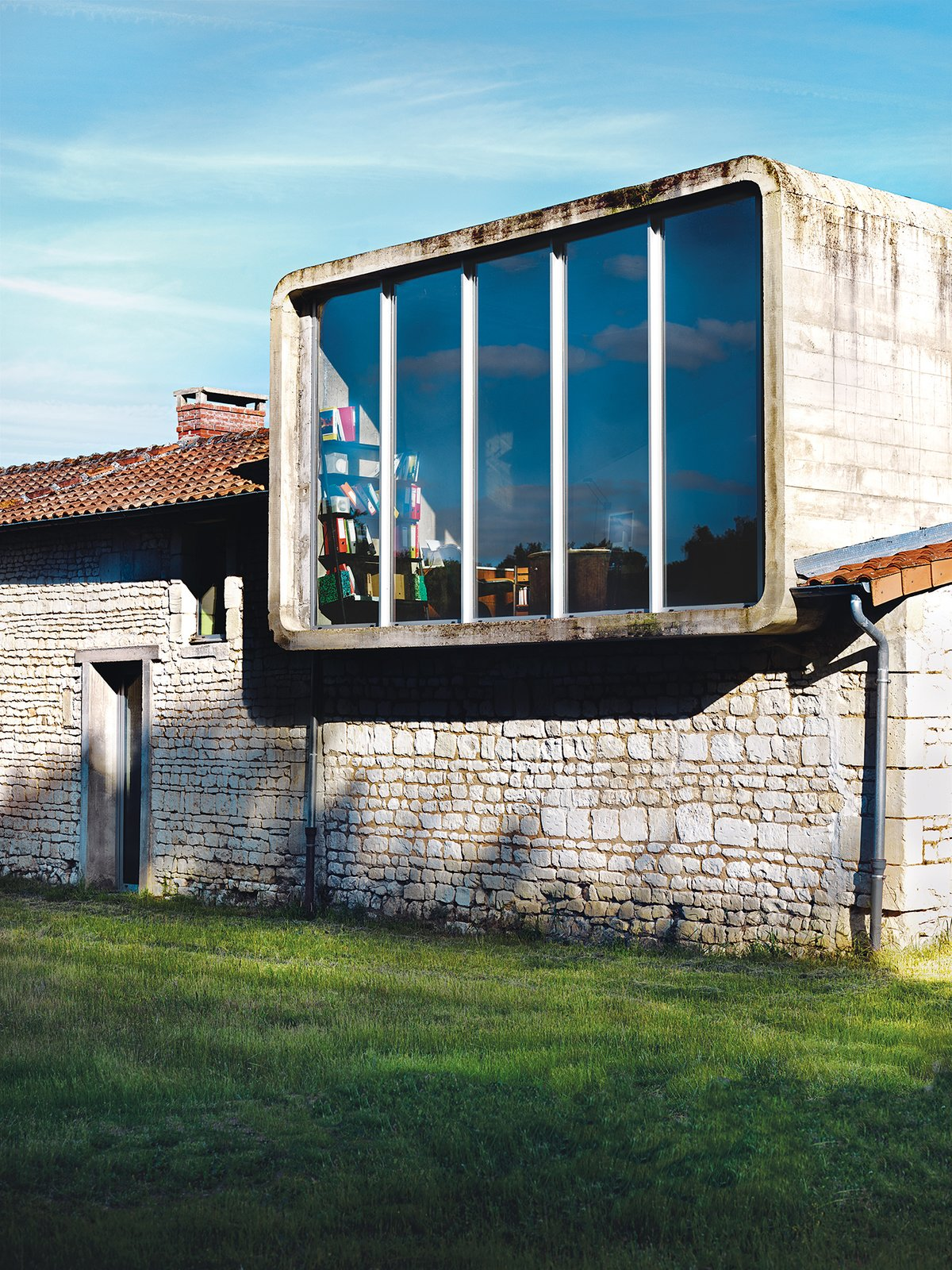 Exterior The second-floor office is housed inside a rounded rectangle of concrete that the architect inserted on top of the old farmhouse.  Farmhouse