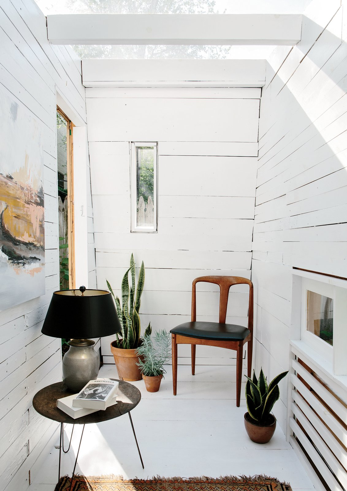 The interior features fence pickets from Hunt's parents' house and a rotating selection of furniture from his apartment.  Studio from An Architect Builds His Own Backyard Oasis From Salvaged Materials