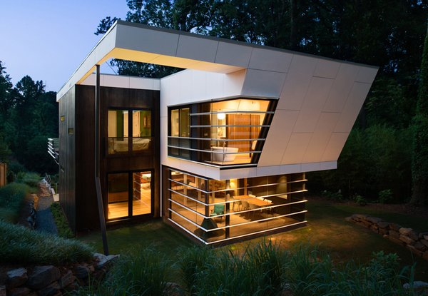 The house features a concrete rainscreen painted gray and Cor-Ten steel paneling around the exterior of the bedrooms. The horizontal louver theme around the dining room windows mimics the vocabulary established on the street-facing facade.