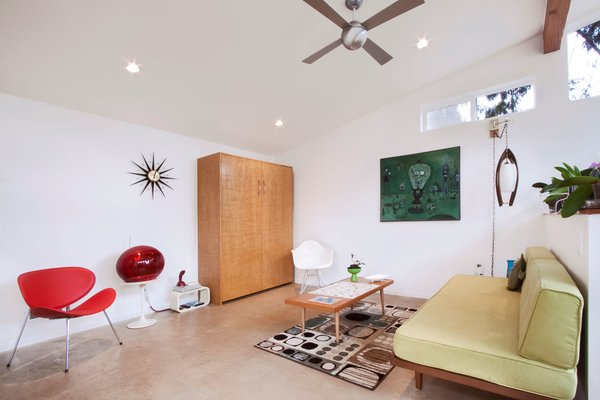 The coffee table, red Memorex video ball TV, and red Mercer candlestick phone are all thrift store finds. The ceiling fan from Modern Fan Company is contemporary, but matches the retro aesthetic.