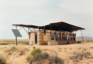 Architect Hank Louis worked with Navajo tribe elders to secure a 66-year lease on a half-acre lot in the middle of Bluf, Utah, for Rosie Joe and her children. The facade of their off the grid house is made up of exposed wood, red rammed earth, and glass.