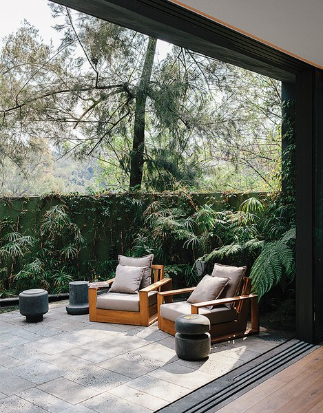 Known for furniture and interior design, Ezequiel Farca transformed a 1970s-style concrete home in Mexico City into a tranquil sanctuary. The temple-like retreat blends into the hilly Lomas de Chapultepec neighborhood with its pale gray-green hue and strategic plantings, which soften the boundaries between house, garden, and street. The Recinto lava stone patio accessed through the living room holds teak outdoor furniture designed by Farca himself.