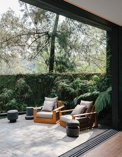 Recinto lava stone lines a patio adjacent to the living room in designer Ezequiel Farca's house in Mexico City. Farca designed the teak outdoor furniture, including two armchairs.