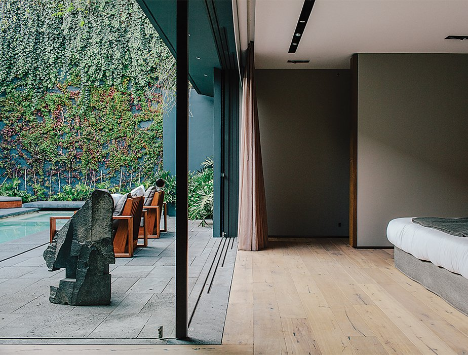 Bedroom and Bed Solid European oak flooring by DuChateau runs throughout the home. The sculpture is by Jorge Yázpik.  Photo 6 of 11 in 10 Retreats in Mexico For the Modernists Who Love the Outdoors from A Lush Retreat With a Sheltered Rooftop Pool in Mexico City