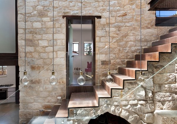 Biophilic design prefers natural over synthetic materials, as human beings innately feel more at ease with the former. In this house in Israel, the limestone walls are recycled from dismantled houses in the region. The stone staircase is original.