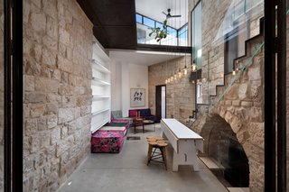 Warm and casual furniture is favored in the courtyard. Colorful seating, wood stools, and smart built-in shelving complete the space. The expandable table by Henkin Shavit is flanked by seven hanging pendant lights, symbolizing the branches of the Menorah. To the right of the table, the original stone arch leads to the home's wine cellar.