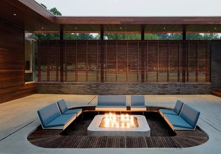 Taking cues from a Japanese-influenced slatted screen applied to the house's facade, Hufft Projects applied a ring of ipe wood around the perimeter of this outdoor firepit.