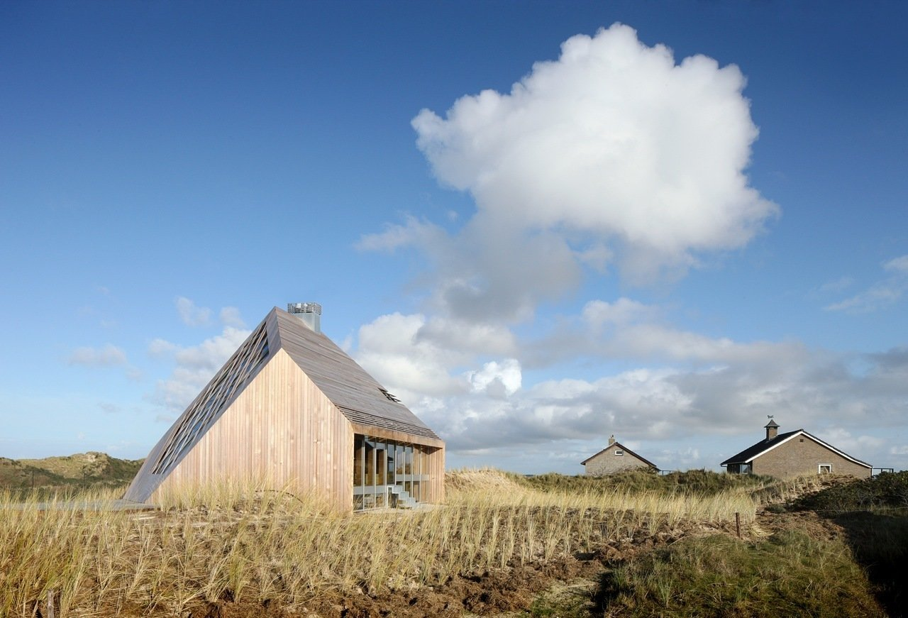 The house is seamlessly integrated into the landscape, at once blending in and sticking out. The exterior cleverly mirrors its surroundings in tone and texture. Solar panels are discretely tucked into the dunes next to the house, and passive building techniques maximize energy efficiency and improve insulation. Wood was favored as both structural and finish material, due to its longevity, recyclability, beauty when aged, and favorable acoustic qualities. Furthermore, since it does not react with salt, wood naturally shields the sea-bordering home from the elements.  Dune House by Sarah Akkoush