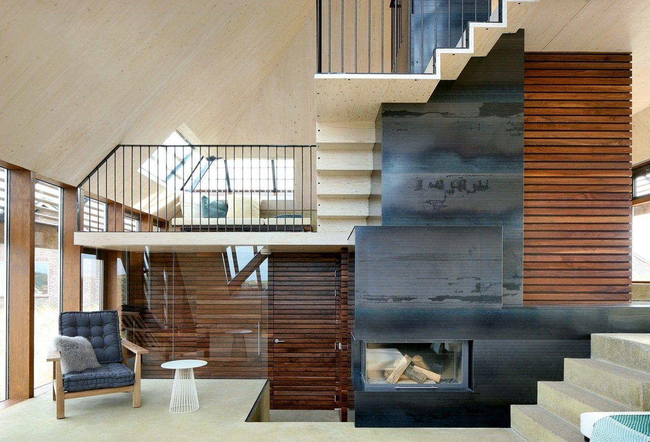 """The interior staircase spirals around the center of the home, in a """"promenade architecturale"""" connecting each level. The continuous and gradual vertical movement is a subtle nod to the experience of strolling through the dunes. A central wood-burning fireplace efficiently heats the whole home, minimizing the need for supplemental in-floor heating incorporated in the concrete floors. Natural cross-ventilation is achieved through the use of CO2 directed grills at the north and south of the home, an added green feature that further reduces the ecological footprint.  190+ Best Modern Staircase Ideas from Dune House"""