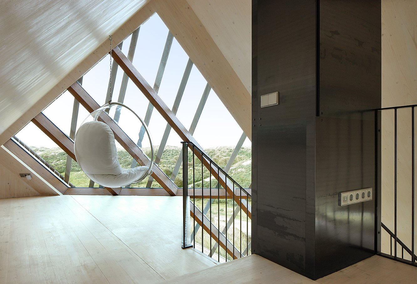 The top floor of the home offers striking views of the surrounding dunes and North Sea. Simply accented with a suspended bubble chair by Aarnio Eero, the viewing platform is the owners' favorite part of the home.  Dune House by Sarah Akkoush