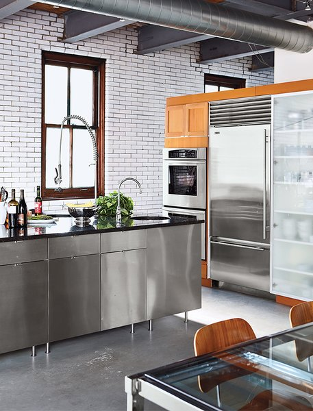 """Kitchen, Concrete, Metal, Metal, Wood, Refrigerator, Wall Oven, and Subway Tile """"The tile, with its sporadic bolts and nails, doesn't need a lot of art, as it is art too,"""" Lisa says. """"The copper windows... Well, you just can't find those anymore.""""  Best Kitchen Refrigerator Metal Photos from Raw Materials Connect this Chicago Renovation with its Industrial Past"""