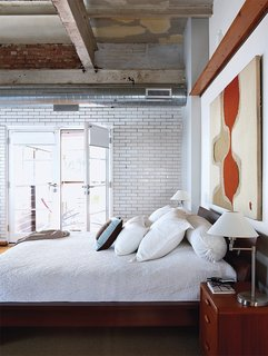 Like the communal spaces, the bedroom features a shining subway tile wall.