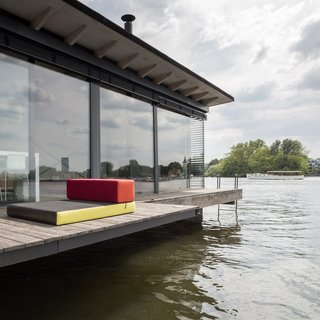A wooden patio wraps around three-fourths of the house boat. The living room cushions can be removed and used on the deck. A ladder dips into the water for swimming in the summer.