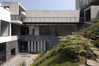 A stone path leads from the backyard, up the hillside, and arrives at the streetside entryway. The rhythmic pattern of the concrete garage, as well as the pedestrian walkway, are front and center. The privacy of the living and sleeping areas, seen at the left through floor-to-ceiling windows, are shielded from public view by the hill and the stone wall.