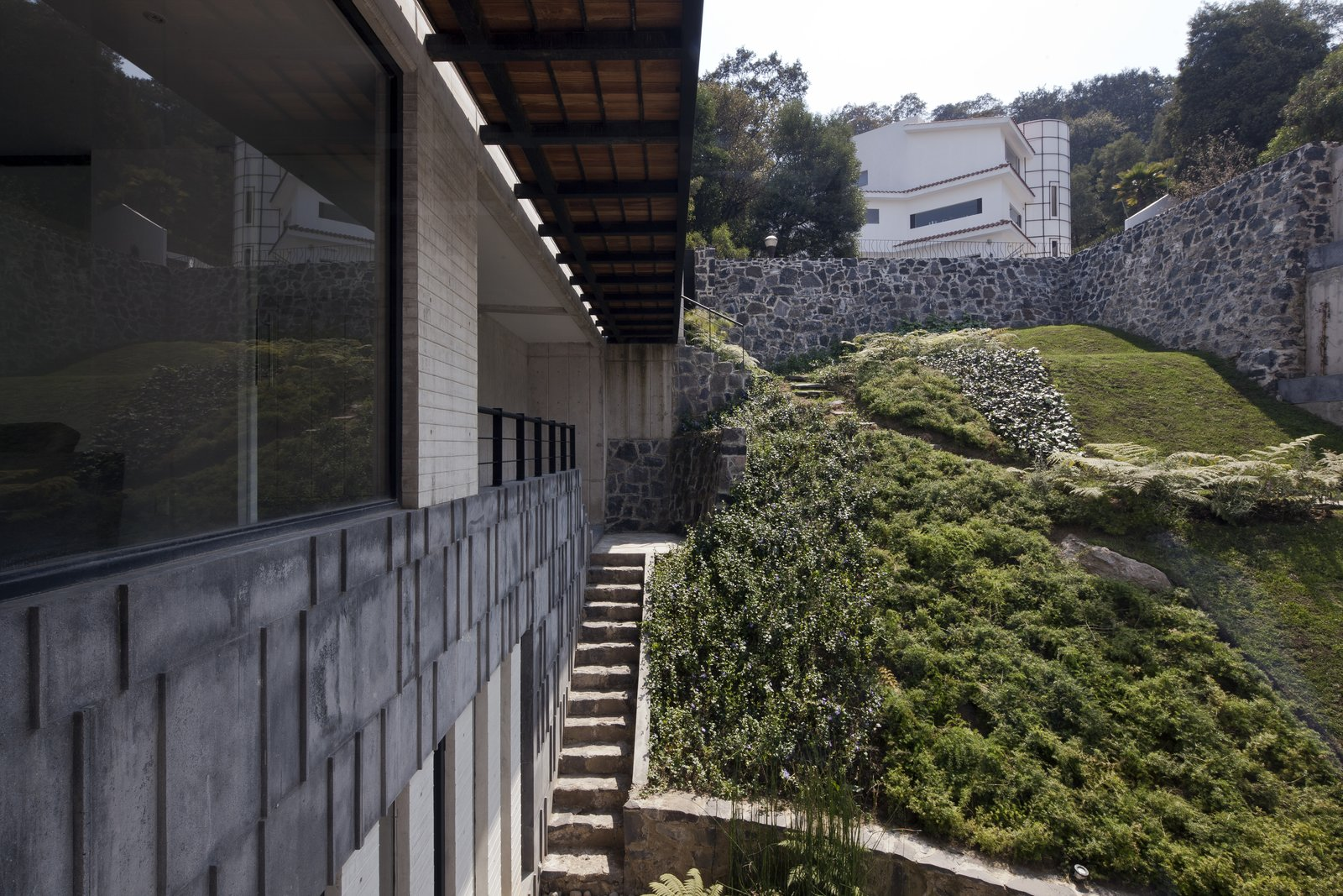 The architects designed a picturesque texture for the hillside that provides a stimulating visual landscape. The recinto stone—seen left—is rhythmically divided by small ridges that also mark the passage of time with their shadows.  Photo 10 of 12 in 5 Reasons Why Landscaping and Bringing Plants Into Your Home Is So Valuable from A Daring Hillside Home Made of Wood, Concrete, and Volcanic Stone