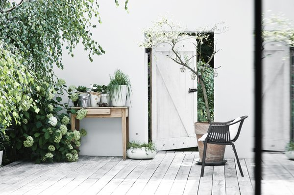 "A door leads out from the romantic courtyard, lush with plants. ""Although we live in a big city, it doesn't feel like it,"" Kolasiński says. ""The neighborhood and the nature are very relaxing and quiet."""