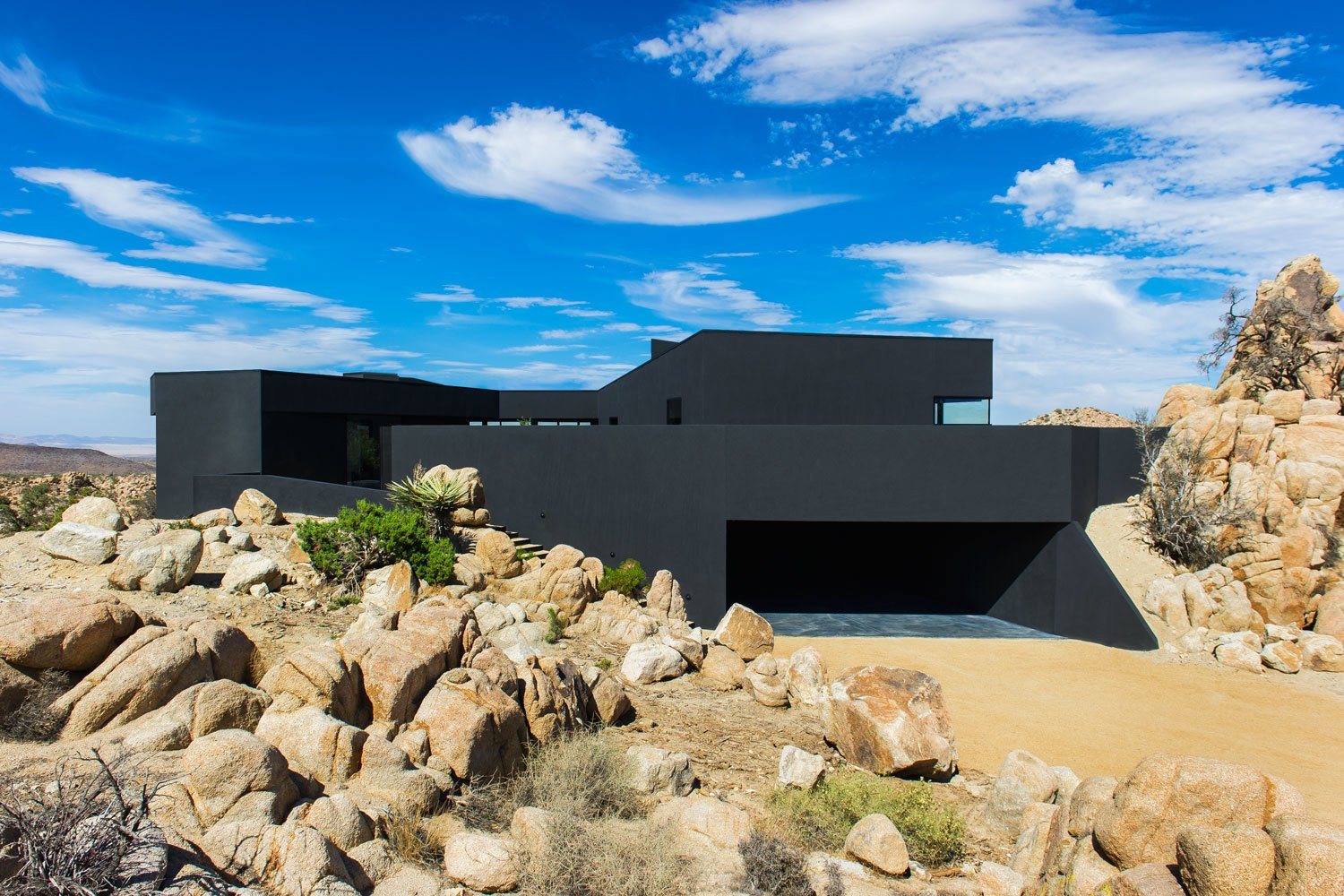 The house seems to claw onto the surrounding landscape, nestled on an outcropping with nearly 360 degree views of the surrounding desert.  A Sculptural Desert Escape Inspired by a Shadow by Caroline Wallis
