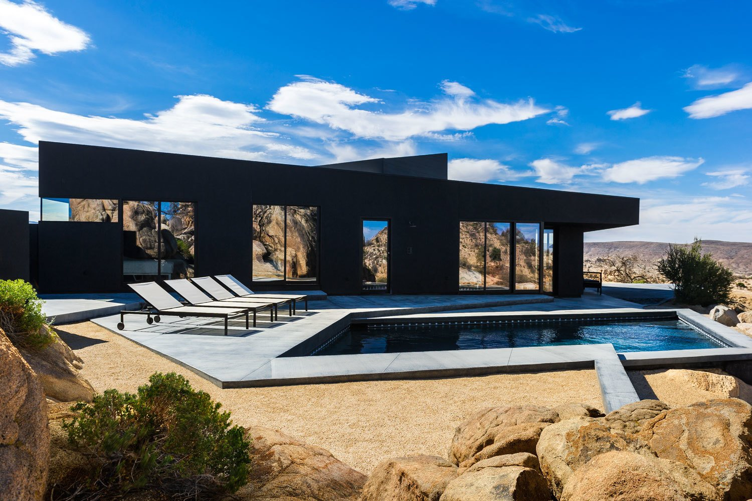 The pool is framed by angular concrete paths reflecting the natural geometry of the site.  Photo 3 of 8 in A Sculptural Desert Escape Inspired by a Shadow