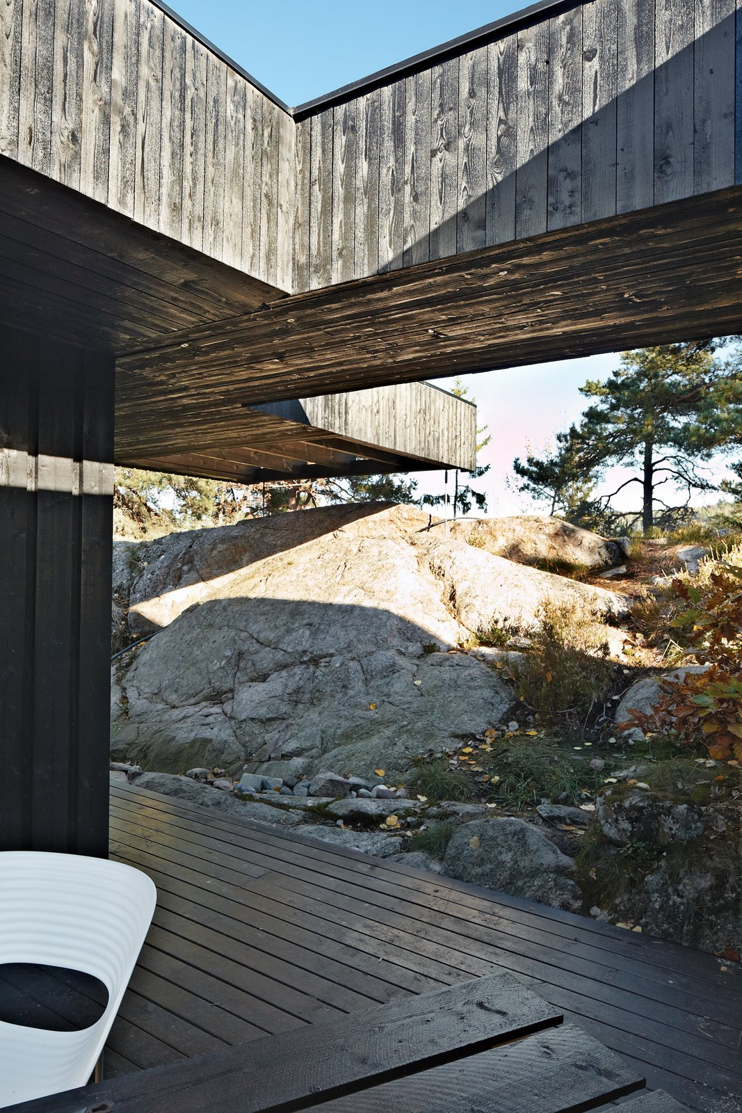 Outdoor, Boulders, Large Patio, Porch, Deck, Wood Patio, Porch, Deck, and Trees A section of the roof reaches over a rock outcropping—a detail that visually connects the house to the landscape and offers a handy way to climb up to the roof deck without using a ladder.  Cabin