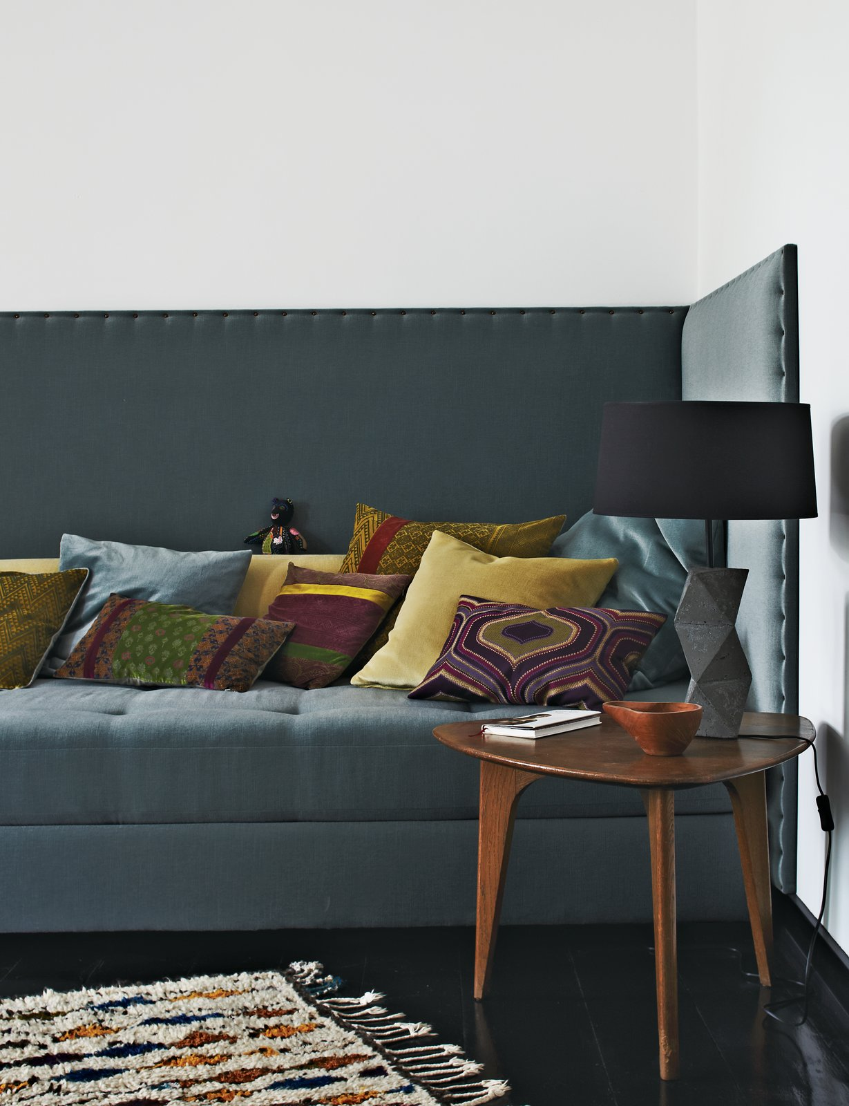 Fehrentz designed the sofa and had it upholstered in fabric by JAB Anstoetz. He cast the concrete base of the table lamp. The 1950s teak coffee table is vintage.  Photo 7 of 11 in Inside Peter Fehrentz's Renovated Flat in Berlin