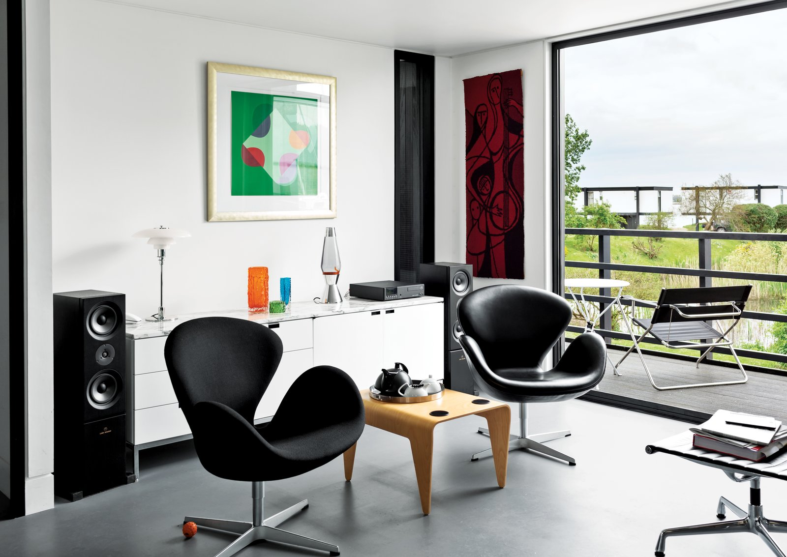 Living Room, Chair, End Tables, Concrete Floor, Lamps, Media Cabinet, and Table Lighting In the living room, Arne Jacobsen Swan chairs flank a Marcel Breuer for Isokon nesting table. Above the Florence Knoll–designed credenza is a print by English artist Terry Frost. The adjacent deck holds Breuer's Folding Armchair and a table from Aram in London.  Photo 2 of 7 in An Elevated Deckhouse in England