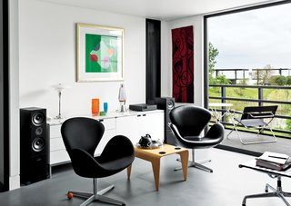In the living room, Arne Jacobsen Swan chairs flank a Marcel Breuer for Isokon nesting table. Above the Florence Knoll–designed credenza is a print by English artist Terry Frost. The adjacent deck holds Breuer's Folding Armchair and a table from Aram in London.