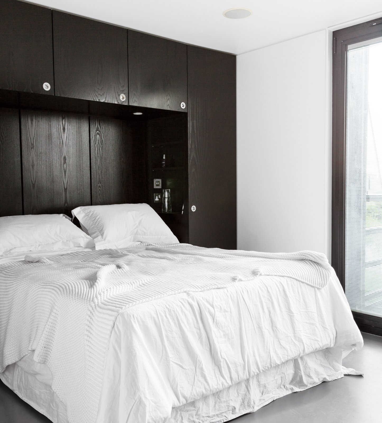 Bedroom, Bed, Concrete Floor, and Storage The master bedroom echoes the house's black-and-white exterior and includes a custom-built storage unit that the architect designed for the space.  Photo 5 of 7 in An Elevated Deckhouse in England